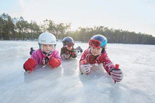 Portrait of girls and boy crawling on frozen lake, Gavle, Swedenの写真素材 [FYI03558139]
