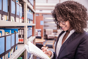 Businesswoman reading file from office shelvesの写真素材 [FYI03558158]