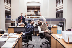 Two businessmen high-fiving in officeの写真素材 [FYI03558175]