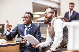 Two businessmen reading paperwork and pointing in officeの写真素材 [FYI03558182]