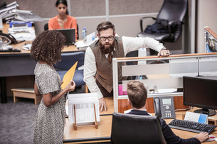 Businesswoman and men talking at office deskの写真素材 [FYI03558194]