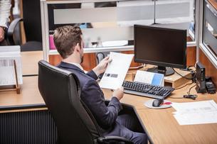 Businessman reading paperwork at office deskの写真素材 [FYI03558197]