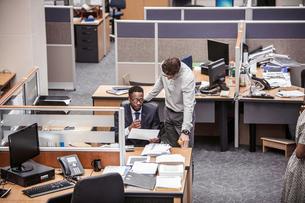 Two businessmen talking at office deskの写真素材 [FYI03558201]