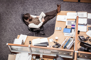 Overhead view of businessman with feet up on office deskの写真素材 [FYI03558203]