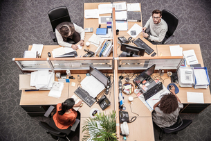 Overhead view of businessmen and women at office deskの写真素材 [FYI03558204]