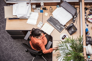 Overhead view of businesswoman busy at office deskの写真素材 [FYI03558206]