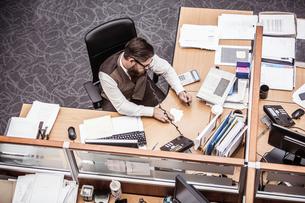 Overhead view of businessman talking on landline at office deskの写真素材 [FYI03558207]