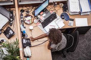 Overhead view of businesswoman talking on landline at office deskの写真素材 [FYI03558211]