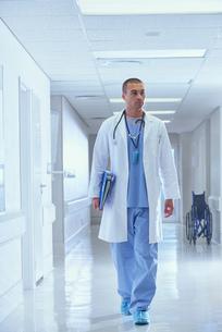 Doctor walking along hospital corridor carrying medical notesの写真素材 [FYI03558226]