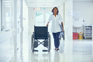 Female orderly pushing wheelchair along hospital corridorの写真素材 [FYI03558227]