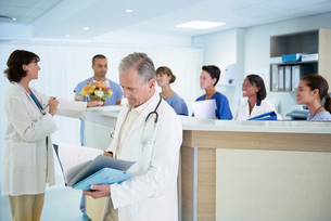 Senior doctor reading medical notes at hospital nurses stationの写真素材 [FYI03558242]