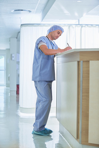 Doctor writing up medical notes at hospital nurses stationの写真素材 [FYI03558245]
