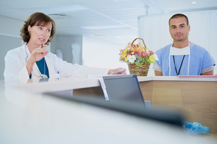 Female doctor talking at nurses station in hospitalの写真素材 [FYI03558247]