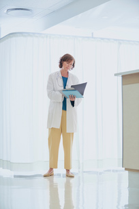 Female doctor reading medical notes at nurses station in hospitalの写真素材 [FYI03558248]