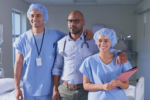 Portrait of mature male doctor and medical team in hospital wardの写真素材 [FYI03558261]