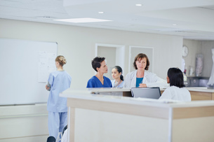 Female doctor having discussion with nurses at nurses station in hospitalの写真素材 [FYI03558266]
