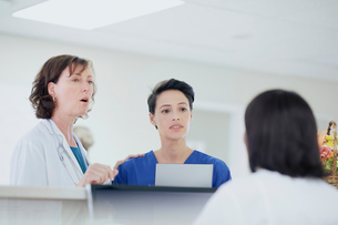 Female doctor having discussion with nurses at nurses station in hospitalの写真素材 [FYI03558267]