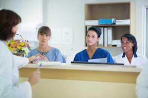 Female doctor having discussion with nurses at nurses station in hospitalの写真素材 [FYI03558270]