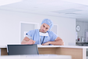 Male doctor writing medical notes at nurses station in hospitalの写真素材 [FYI03558274]