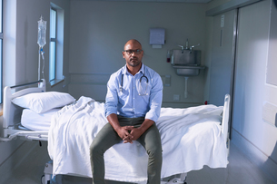 Portrait of mature male doctor sitting on hospital bed in wardの写真素材 [FYI03558290]