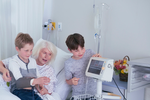 Senior female patient in hospital bed with grandsons playing with blood pressure machineの写真素材 [FYI03558297]