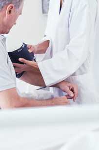 Cropped shot of female doctor using blood pressure gauge on senior male patient on hospital bedの写真素材 [FYI03558302]