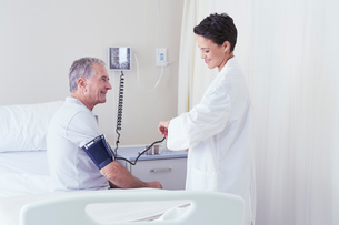 Female doctor using blood pressure gauge and timing pulse of senior male patientの写真素材 [FYI03558303]