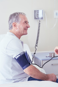 Senior male patient having blood pressure taken by doctorの写真素材 [FYI03558304]