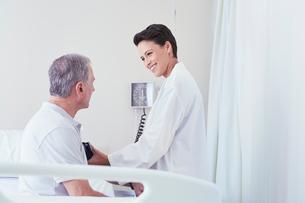Female doctor using blood pressure gauge on senior male patient on hospital bedの写真素材 [FYI03558305]