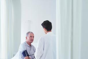 Senior male patient having blood pressure blood pressure gauge taken by female doctorの写真素材 [FYI03558306]