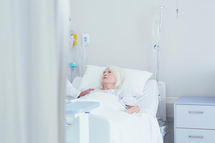 Doctor talking to worried senior female patient in hospital bedの写真素材 [FYI03558307]
