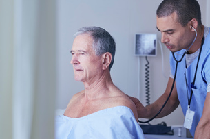 Male nurse listening to senior male patient back with stethoscopeの写真素材 [FYI03558310]