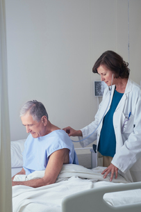 Female doctor listening to senior male patient back with stethoscopeの写真素材 [FYI03558311]