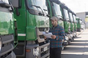 Man by fleet of trucks looking at paperworkの写真素材 [FYI03558338]