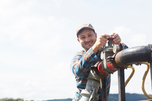 Man opening valve on industrial piping, looking at camera smilingの写真素材 [FYI03558346]