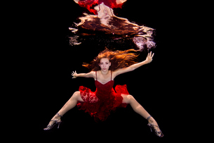 Underwater view of girl wearing red dress and high heeled shoesの写真素材 [FYI03558439]