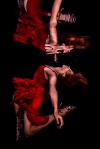 Underwater view of girl wearing red dress and high heeled shoes, reflected in water surfaceの写真素材 [FYI03558464]