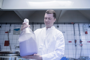Scientist carrying large bottle of chemical in laboratoryの写真素材 [FYI03558513]