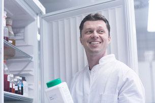 Scientist holding bottle of chemical removed from cabinetの写真素材 [FYI03558516]