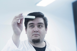 Scientist examining sample in test tubeの写真素材 [FYI03558537]
