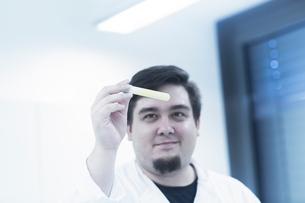 Scientist examining sample in test tubeの写真素材 [FYI03558543]