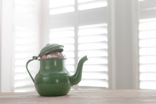 Green vintage teapot full of British coins on tableの写真素材 [FYI03558560]