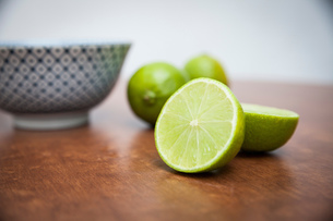 Halved and whole limes on wooden tableの写真素材 [FYI03558614]