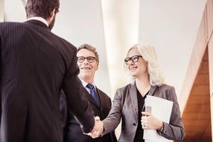 Businessmen and woman shaking hands in office corridorの写真素材 [FYI03558642]