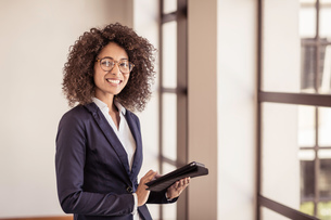 Portrait of young businesswoman using digital tablet in officeの写真素材 [FYI03558666]