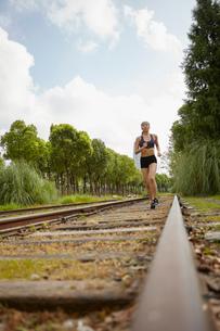Woman jogging on railway trackの写真素材 [FYI03558738]