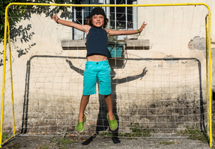 Boy in football goal jumping in mid airの写真素材 [FYI03558794]