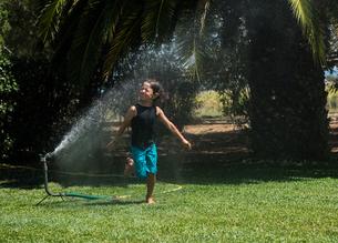 Boy running through water from garden sprinklerの写真素材 [FYI03558801]