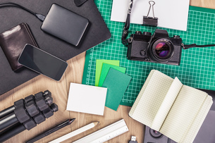 Overhead view of retro camera, notebook, diary, external hard drive, wallet, tripod and smartphoneの写真素材 [FYI03558874]