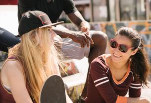 Two female friends chatting in city skateparkの写真素材 [FYI03558894]